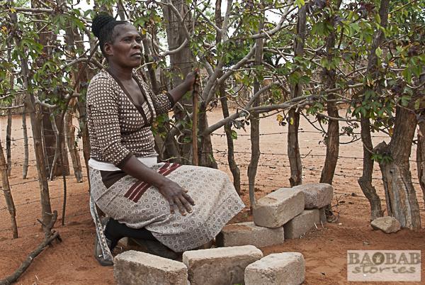 Sylvia Matoho mit Baobab-Setzling, hinter Stock